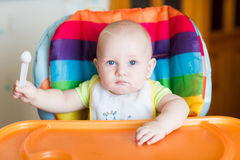Adorable baby eating in high chair Royalty Free Stock Photos