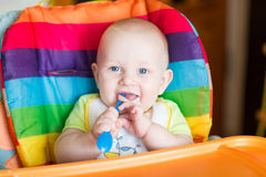 Adorable baby eating in high chair Stock Photography