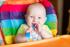 Adorable baby eating in high chair Stock Photo