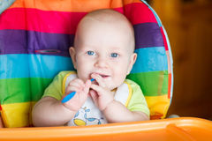 Adorable baby eating in high chair Royalty Free Stock Images