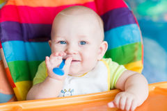 Adorable baby eating in high chair Stock Image