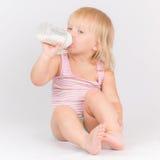 Adorable Baby Eating Milk Sitting On Floor Stock Photos