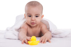 Adorable baby enjoy and looking at yellow duck after bath Royalty Free Stock Photography