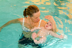 Adorable baby enjoying swimming in a pool with his mother. Lugano, Switzerland - 9 February 2005: Adorable baby enjoying swimming in a pool with his mother stock photography