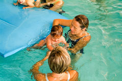 Adorable baby enjoying swimming in a pool with his mother Stock Photo