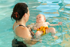 Adorable baby enjoying swimming in a pool with his mother Royalty Free Stock Images