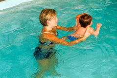 Adorable baby enjoying swimming in a pool with his mother Stock Photos