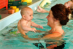 Adorable baby enjoying swimming in a pool with his mother. Lugano, Switzerland - 18 October 2007: Adorable baby enjoying swimming in a pool with his mother royalty free stock photos