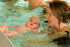 Adorable baby enjoying swimming in a pool with his mother. Lugano, Switzerland - 18 October 2007: Adorable baby enjoying swimming in a pool with his mother stock photo