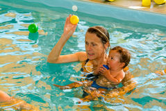 Adorable baby enjoying swimming in a pool with his mother. Lugano, Switzerland - 18 October 2007: Adorable baby enjoying swimming in a pool with his mother royalty free stock images
