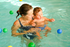 Adorable baby enjoying swimming in a pool with his mother Royalty Free Stock Image