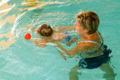 Adorable baby enjoying swimming in a pool with his mother Royalty Free Stock Photography