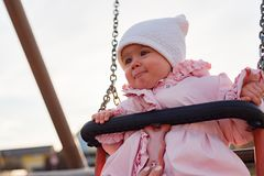 Adorable baby girl with big beautiful eyes and a beanie having fun on a swing