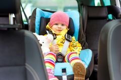 Adorable baby girl with blue eyes and in colorful clothes sitting in car seat. Toddler child in winter clothes going on. Adorable baby girl with blue eyes stock photo