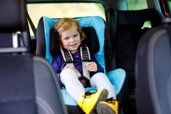 Adorable baby girl with blue eyes sitting in car safety seat. Toddler child going on family vacations and jorney. Happy royalty free stock photos