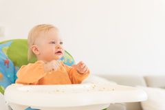Adorable baby girl with blue eyes sitting in the highchair and have a lunch. Stock Photos