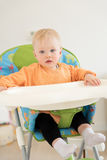Adorable baby girl with blue eyes sitting in the highchair. Stock Photography