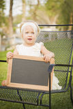 Adorable Baby Girl in Chair Holding Blank Blackboard Royalty Free Stock Photography