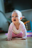 Adorable baby girl crawls on all fours floor at Royalty Free Stock Photos