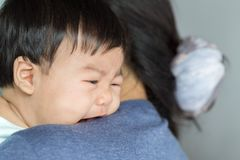 Adorable baby girl cry on mom shoulder. Adorable baby girl cry on mom shoulder Royalty Free Stock Photography