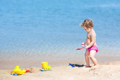 Adorable baby girl with curly hair on beach with toys Royalty Free Stock Photo