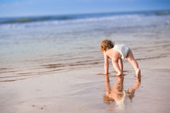 Adorable baby girl with curly hair on beach Royalty Free Stock Photography
