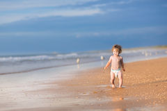 Adorable baby girl with curly hair running on beach Royalty Free Stock Photos