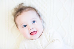 Adorable baby girl with curly hair on a white cabl Royalty Free Stock Image