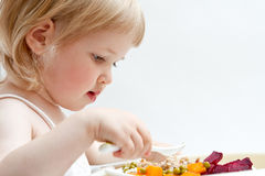Adorable baby girl eating fresh vegetables Royalty Free Stock Photo