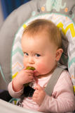 Adorable baby girl eating a pickle for the first time Stock Photos
