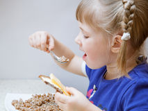 Adorable baby girl eating porridge Royalty Free Stock Photo