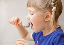 Adorable baby girl eating porridge Royalty Free Stock Images