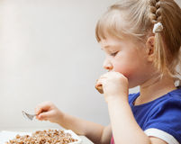 Adorable baby girl eating porridge Stock Photos