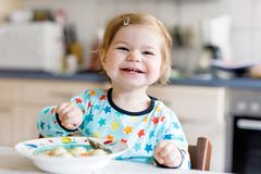 Adorable baby girl eating from spoon vegetable noodle soup. food, child, feeding and development concept. Cute toddler. Daughter with spoon sitting in royalty free stock image