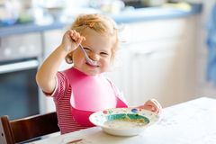 Adorable baby girl eating from spoon vegetable noodle soup. food, child, feeding and development concept. Cute toddler. Child, daughter with spoon sitting in stock images