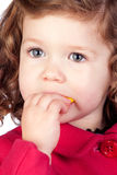 Adorable baby girl eating sweets Royalty Free Stock Photos