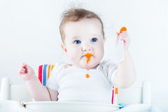 Adorable baby girl eating vegetables for the first time Royalty Free Stock Image