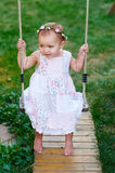 Adorable Baby Girl Enjoying A Swing Ride On A Playground In A Park Stock Image