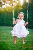 Adorable baby girl enjoying a swing ride on a playground in a park Stock Images