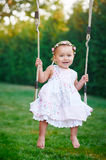 Adorable baby girl enjoying a swing ride on a playground in a park Stock Photos