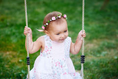 Adorable baby girl enjoying a swing ride on a playground in a park Royalty Free Stock Photography