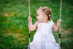 Adorable baby girl enjoying a swing ride on a playground in a park Stock Photography