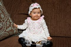 Adorable Baby Girl in Eyelet Dress and Hat Poses for the Camera. An adorable, baby girl in an eyelet dress with hat posing for the camera. She is wearing a stock photo