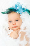 Adorable baby girl with flower in her hair. Beautiful adorable baby girl with fashion flower in her hair, lying in fluffy feathers Royalty Free Stock Photos