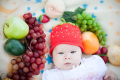 Adorable baby girl in the fruits Stock Photography