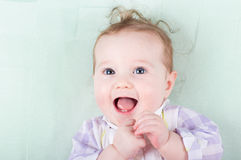Adorable baby girl with funny curly hair laughing happily. Adorable little baby girl with funny curly hair laughing happily Royalty Free Stock Photos