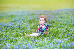 Adorable baby girl in garden with lots of blue flowers Royalty Free Stock Photos