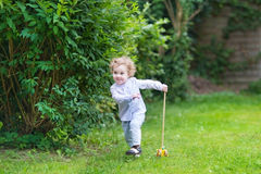 Adorable baby girl in the garden with wooden toy Royalty Free Stock Photos