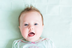 Adorable baby girl on a green knitted blanket smiling Stock Photography