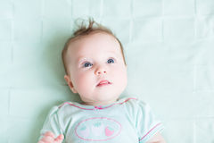 Adorable baby girl on a green knitted blanket smiling Royalty Free Stock Image